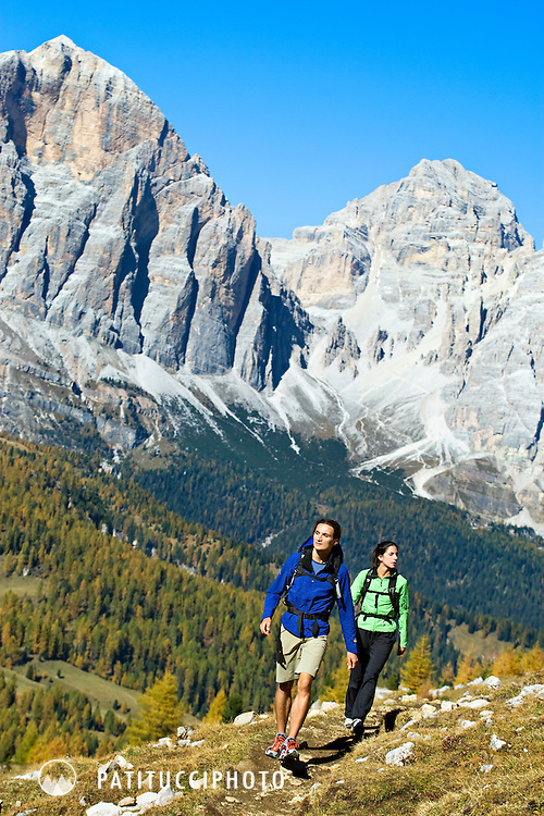 Filippo Tosoratti and Amy Fountain hiking the Alta Via 1 trail on the Passo Giau, high above Cortina, Italy on a clear and sunny fall day
