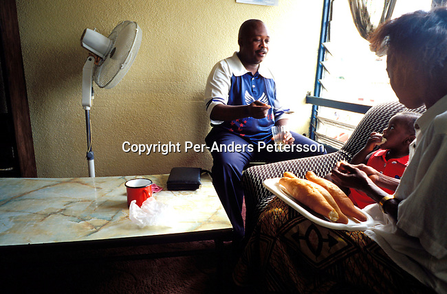 dicocon00202.Congo. Kinshasa. Family, mother, father and baby. Kabanga Makolo Robert, age 48, and his wife Kiawanga Marie Robert, age 38, and their baby Apika eating breakfast in the living room of their flat on February 28, 2002 in Lingwala district in Kinshasa, Congo. Mr. Robert has lived in the 2 room flat for 20 years. He is a junior bank inspector at a local bank, and his wife is a housewife. They live a middle class life in Kinshasa, a few of the lucky ones to have a job that pays a little bit more than being an civil servant. Civil servants are paid about $ 10 a month in Congo. Fan..©Per-Anders Pettersson/iAfrika Photos