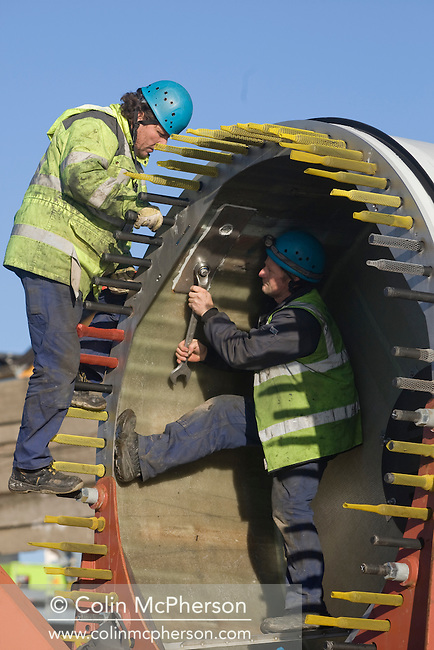 Engineers on the ground working on the last remaining 11 tonne blade on a 2.5 megawatt wind turbine at Alexandra Dock in Liverpool.  The three 45 metre blades were lifted onto the 80 metre towers using two cranes and were assembled by a team from Germany after arriving in sections from the manufacturers in Rostock. The month-long operation was undertaken by the docks' owners, Peel Holdings, and was a £15m investment which will generate power for the docks and around 5500 nearby homes.