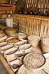 Bali, Indonesia; coffee beans in wicker baskets inside a thatched hut