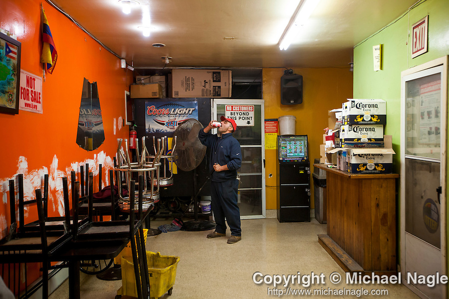 QUEENS, NY -- OCTOBER 25, 2013:  Christopher Canale, 51, sips a beer as he mops the floor of the Master Express Deli & Restaurant in Willets Point on October 25, 2013 in Queens, NY.  PHOTOGRAPH  BY MICHAEL NAGLE FOR THE NEW YORK TIMES