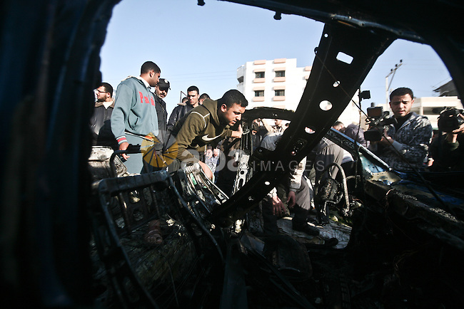 Palestinians look at the remains of a vehicle after it exploded in Gaza City March 9, 2012. Israel killed the leader of a Palestinian militant faction on Friday in a targeted attack on the car in the Gaza Strip, an Israeli official said. A second man also died in the blast, and a third was injured. The attack came shortly after two rockets were fired at Israel from the coastal territory, causing no damage or injury. Photo by  Ali Jadallah