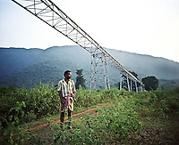 A villager, who once owned this land, stands below the unfinished conveyor designed to transport bauxite ore from the Niyamgiri hills to the Vedanta Alumina plant. The huge bauxite deposits in the Niyamgiri hills have led the Vedanta group to set up an alumina refinery at Lanjigarh, making the local population of Dongria Kondh tribespeople fearful for their future. Vedanta Resources has come under immense pressure from human rights and environmental groups to abandon its plans to mine at the Niyamgiri mountains, as the site is considered sacred by the local tribal community..