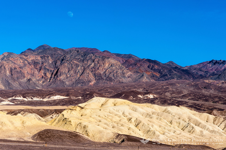 United States, California, Death Valley. The Moon rises above the mountain range. View from Harmony Borax Works.