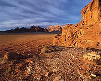 Sandstone mountains rise from the desert sands in warm evening light in Wadi Rum, Jorda