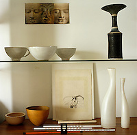 A collection of pottery and porcelain on display on a glass shelf