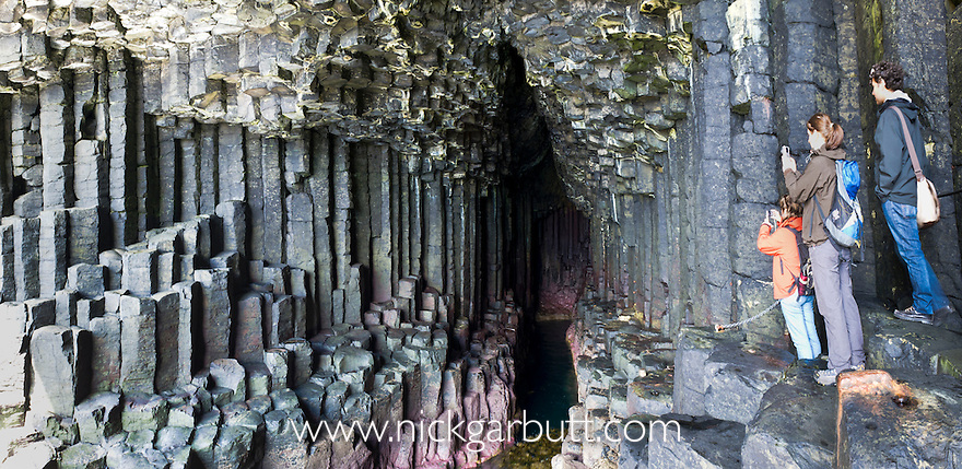 Tourists at the entrance to Fingal's Cave, Isle of Staffa, off the Isle of Mull, Scotland.