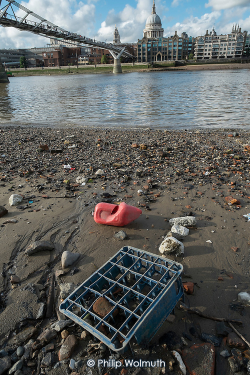 Rubbish washed up on the River Thames at low tide opposite St Pauls Cathedral London