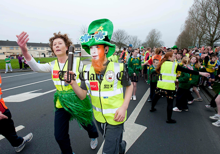 Tariq El Masri from St Caimin's Secondary School takes up the baton in the company of his teacher, Ailís Power, during the Rith 2012 Irish Language Relay Race in Shannon. Photograph by Declan Monaghan