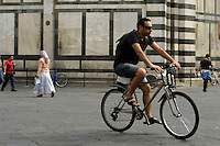 Ciclisti in piazza San Giovanni, vicino al Battistero. Cyclists in Piazza San Giovanni, near the Baptistery..