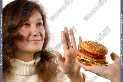 Young smiling woman refusing to eat a hamburger. Showing a stop gesture. Healthy eating and dieting conceptual portrait. Isolated silhouette on white background. The woman has half korean half european ethnicity