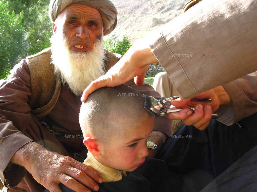 AFGHANISTAN - VALLEE DU PANJSHIR - POSHGHOUR - 15 aout 2009 : Coiffeur ambulant dans le village de Poshghour. ..AFGHANISTAN - PANJSHIR VALLEY - POSHGHOUR - August 15th, 2009 : Travelling barber in the town of Poshghour.