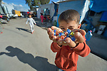 A boy plays with marbles in a camp for internally displaced families in Ankawa, near Erbil, Iraq. Residents of the camp, mostly Christians, were displaced from Mosul, Qaraqosh and other communities in Iraq when ISIS swept through the area in 2014.