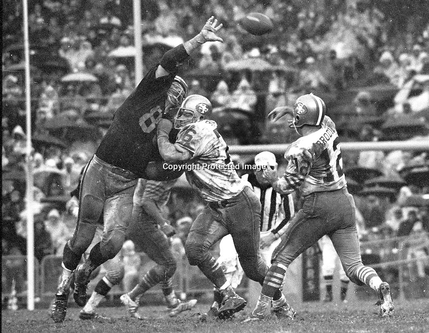 49er QB JohnBrodie throws pass over Oakland Raider end Ben Davidson. (1970 photo/Ron Riesterer)