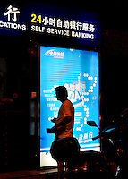 A man stands next to bank's 24h self-service banking, Chengdu, China. 24h self-service banking, include cash deposit, withdraw and passbook entry. Those services can save customers' time for queuing up and can support banking services in the not-office hours..