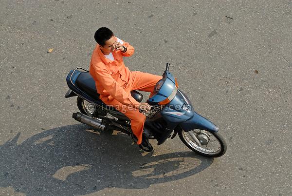 Asia, Vietnam, Hanoi. Hanoi old quarter. Vietnamese man, while using his mobile phone, riding on a small motorbike through Hanoi.