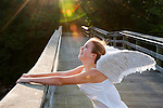 Joyful Angel teen girl with feather wings and sleeveless white dress Looking Up to Sun Flare at wood pier, with arms stretched out holding onto flat wood railing of long pier.