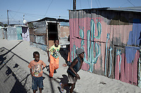 Khayelitsha, South Africa March 5, 2013: Boys play in the residential area next to Amandla EduFootball grounds, which was founded by Jakob Schlichtig, Florian Zech outside the field in Khayelitsha a poor township outside Cape Town, South Africa. They use football to initiate, support educational projects for youth in the township. The program keep children busy and it decreases the risk of them joining gang, criminal activity or teenage pregnancy. The crime level has decreased substantially in the area since the program was created in 2006. (Photo by: Per-Anders Pettersson)