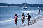 Itaparica Island, Brazil. Three mulatta girls walking on a beach with a yacht behind. Bahia State.