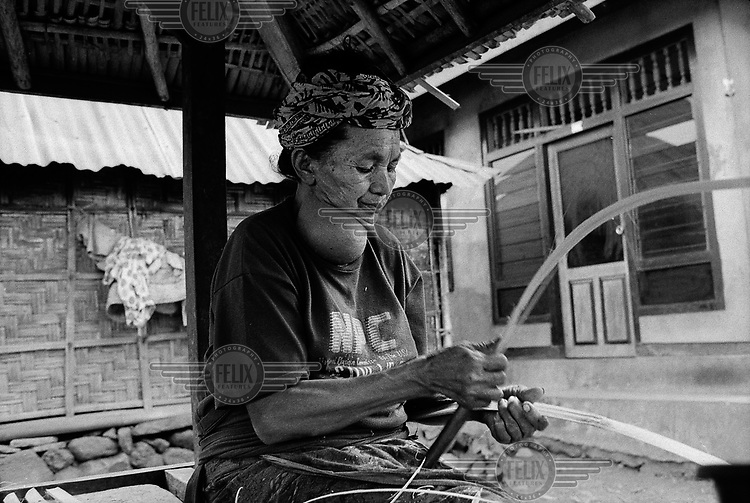 A woman with a goiter, the result of Iodine deficiency, weaves bamboo in a remote mountain village in Bali.