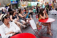 New York,, NY 29 August 2015 Tourists sit in the pedestrian plaza in Times Square enjoying desnudos - topless women whose bodies have been painted red white and blue.