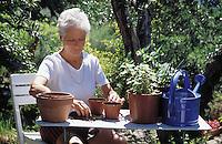 A senior woman potting plants in her garden.