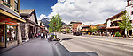 Panoramic street scenery of Banff Avenue, main street in the Town of Banff in Alberta Rockies with its gift shops and restaurants and Rocky Mountains in the background. Alberta, Canada 2017