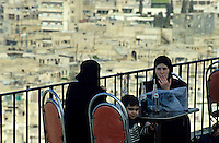 Two women sitting on a cafe terrace, one smoking a cigarette, Aleppo, Syria.