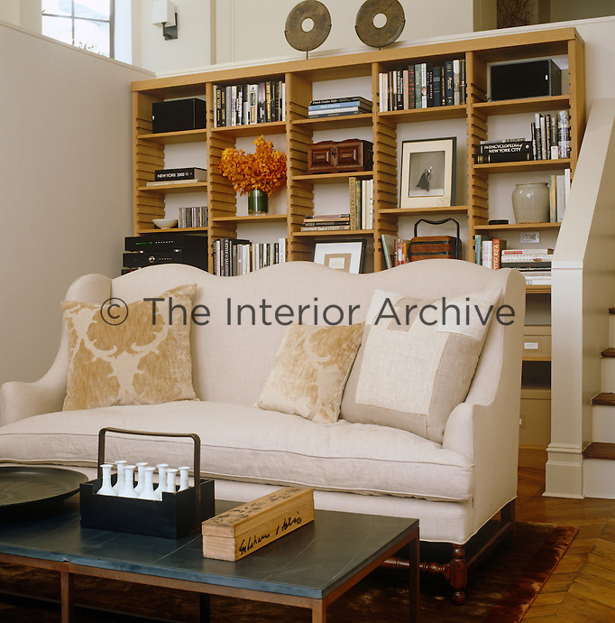 A 19th century copy of a canape sofa in the living room has a storage unit designed by Axel Vervoodt on the wall behind
