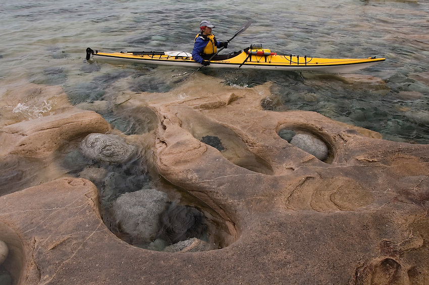 A sea kayaker paddles close to the eroded sandstone shoreline at Grindstone Point in Lake Superior Provincial Park near Wawa Ontario Canada.