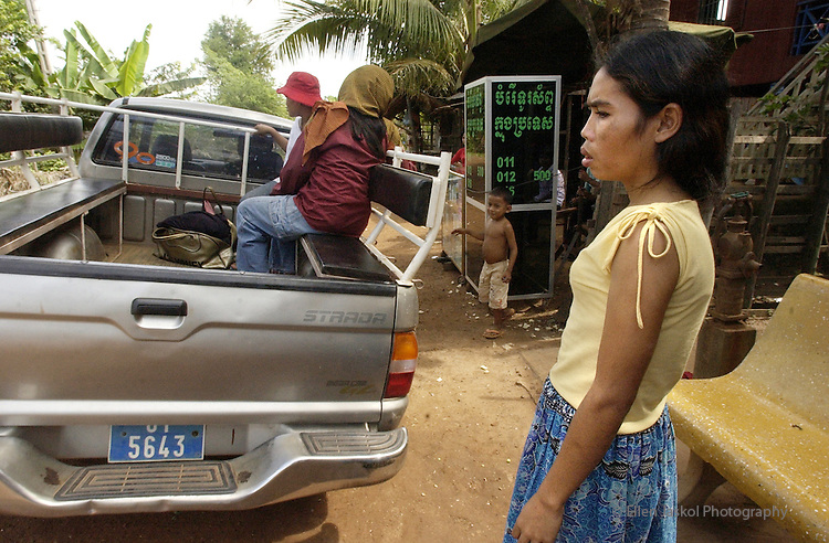 Prostitute Srey Oun Sim, 24,  rt, stays behind at her brotherl, as two other women--one is a prostitute, and one escaped from a brothel owner--drive off in the back of the Kampuchea for Christ's (KFC's) truck to take them to the women's center.    KFC had tried to purchase Srey Oun and two other prostitutes (not on the truck) from a brothel, but the owner at the last minute increased the price and KFC couldn't purchase them.   (ELLEN JASKOL/ROCKY MOUNTAIN NEWS)..