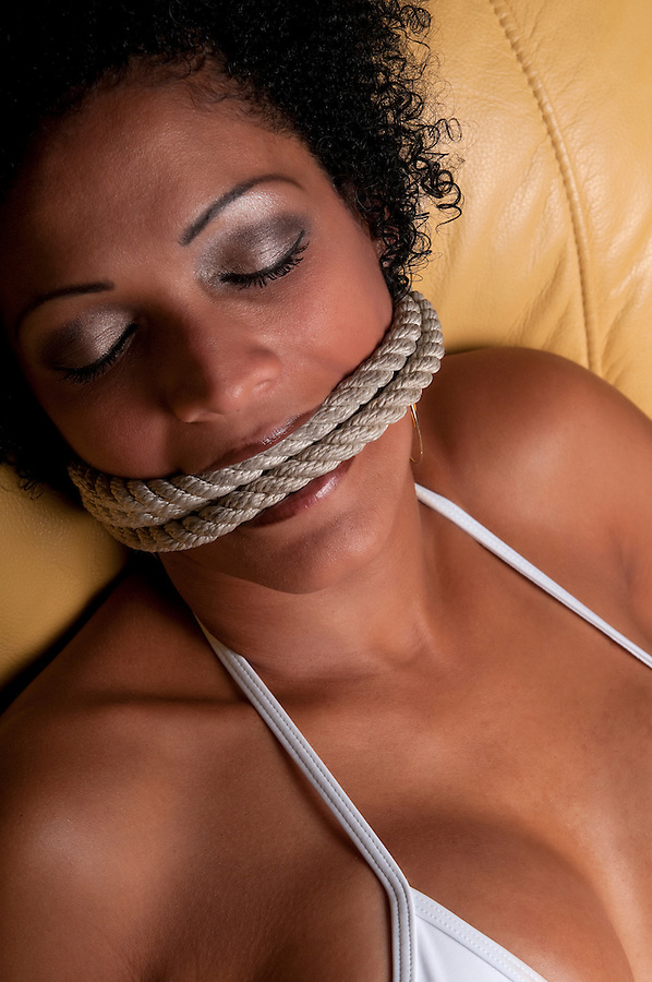 Abused bruneete woman dismayed with rope bondage.
