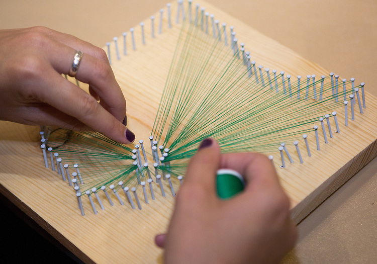 Samantha O'Brien completes her Ohio University-themed string art piece during a Homecoming how-to event hosted by the Campus Involvement Center in Baker Center Theater Lounge on Oct. 7, 2014. Photo by Lauren Pond