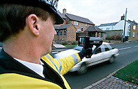 Traffic police officer performing speed enforcement checks using a handheld laser equipped speed measuring device. The officer points the unit at an on-coming vehicle and the speed is shown on the back of the gun. This image may only be used to portray the subject in a positive manner..©shoutpictures.com..john@shoutpictures.com