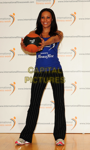 MELANIE BROWN aka MEL B .Launches The International Fitness Week, Fitness First Gym, Tottenham Court Road, London, England..January 28th, 2010.photocall full length medicine ball blue black pinstripe striped trousers trainers top tattoo basket holding vest exercise scary spice .CAP/CJ.©Chris Joseph/Capital Pictures.