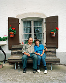 SWITZERLAND, Motiers, Lutin and his wife Giselle du Jura sit and sip on Absinthe in front of their home, Jura Region