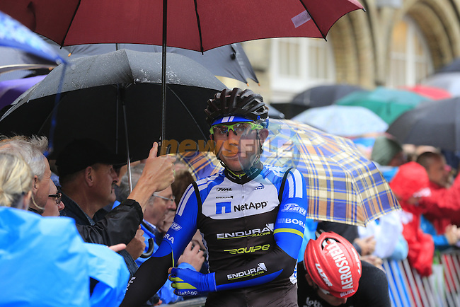 Netapp-Endura rider takes shelter from spectators as he waits on the start line in Ypres before the start of the cobbled stage Stage 5 of the 2014 Tour de France running 155.5km from Ypres to Arenberg. 9th July 2014.<br /> Picture: Eoin Clarke www.newsfile.ie