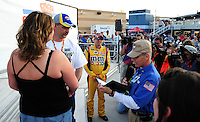 Feb. 27, 2009; Las Vegas, NV, USA; NASCAR Sprint Cup Series driver Kyle Busch (center) jokingly acts as the best man as fans Heather Landry and Damon Landry get married in victory lane following qualifying for the Shelby 427 at Las Vegas Motor Speedway. Mandatory Credit: Mark J. Rebilas-
