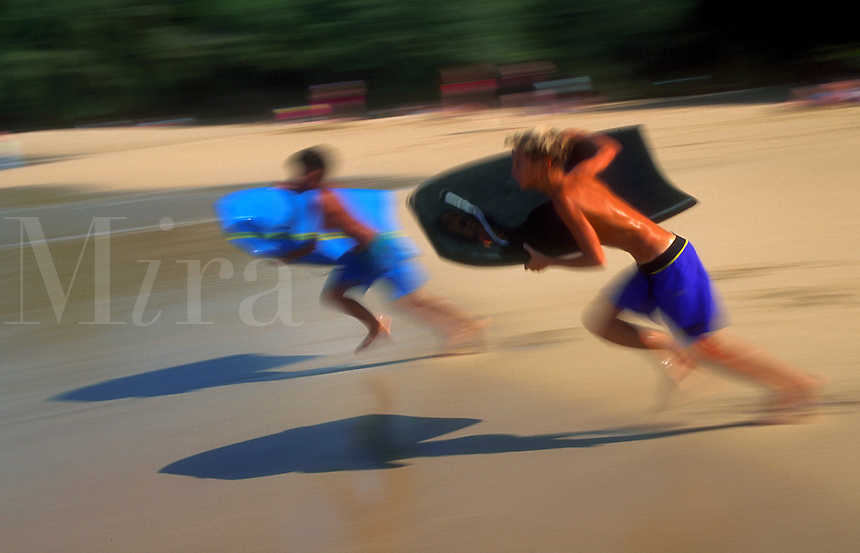 Blurred motion image of two boys running on the sand with boogie boards. Hawaii.