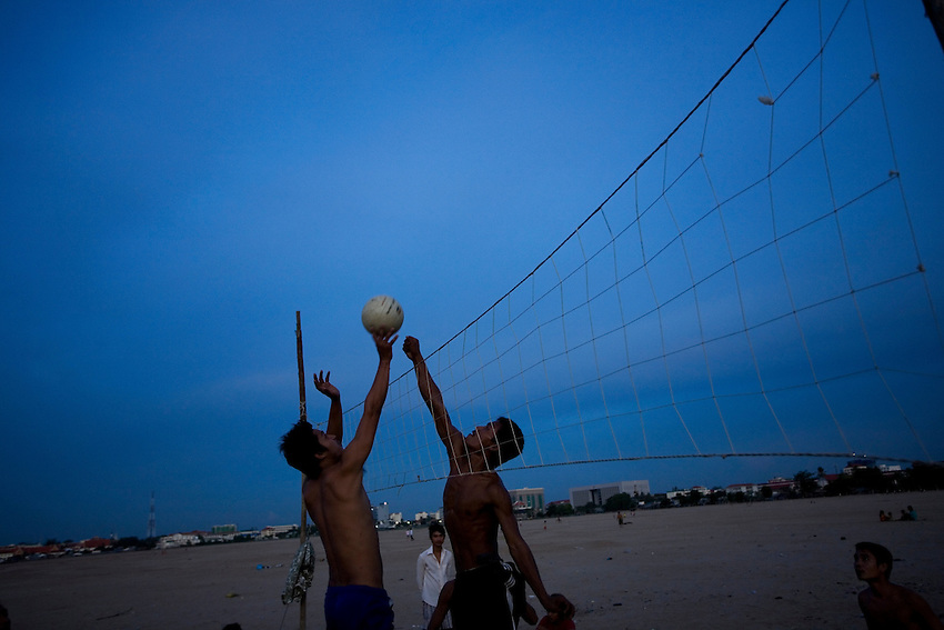 Residents who face eviction from the Boeung Kak Lake area in central Phnom Penh play volleyball on an area of sand where the lake is in the process of being filled in, Phnom Penh, Cambodia, June 11, 2010. More than 4,000 families will be evicted from their homes as part of the 133-hectare Boeung Kak Lake development project which is being carried out by Shakuku Inc. In 2007 authorities awarded a 133-hectare swathe around Boeung Kak lake to Shukaku Inc, which is headed by Cambodian People's Party Senator Lao Meng Khin. Housing rights advocates say the villagers have a right to claim ownership of the land, on which many have lived for years..