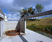 The minimal concrete terrace has a cedarwood hot tub in a secluded corner