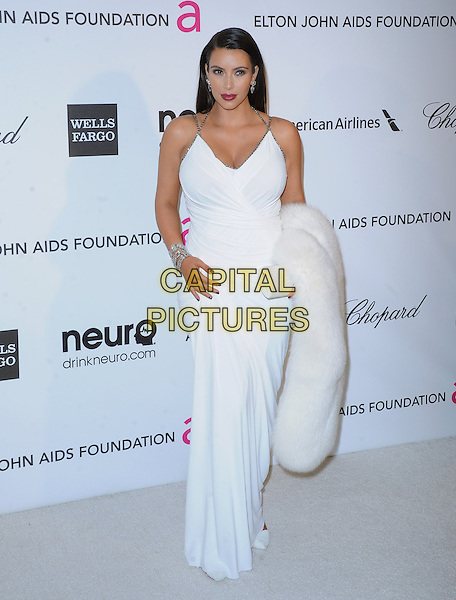 Kim Kardashian.The 21st Annual Elton John AIDS Foundation Academy Awards Viewing Party held at The City of West Hollywood Park in West Hollywood, California, USA..February 24th, 2013.oscars full length white sleeveless dress carrying fur pregnant diamond bracelet halterneck .CAP/DVS.©DVS/Capital Pictures.