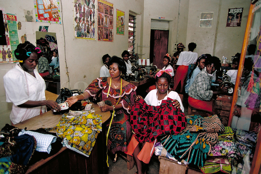 Workers in this small tailoring shop, located in Kumasi, Ghana (Africa) share the pride, respect and dignity that comes from being productive members of Ghana's modern society. occupations, trade, clothing, fashion, women. Tailoring shop in Ghana, Africa.