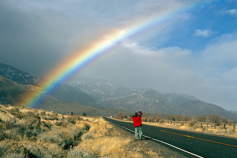 Man photographing rainbow on highway near Cedarville. Nevada