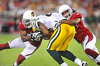Aug. 28, 2009; Glendale, AZ, USA; Green Bay Packers tight end (88) Jermichael Finley is tackled by Arizona Cardinals safety (24) Adrian Wilson and safety (41) Rashad Johnson during a preseason game at University of Phoenix Stadium. Mandatory Credit: Mark J. Rebilas-