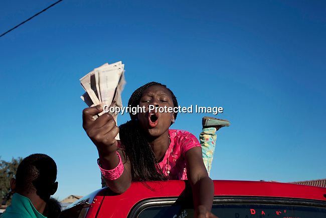 SOWETO, SOUTH AFRICA SEPTEMBER 29: An Izikhothane girl displays cash on September 29, 2012 in Thokoza Park, Soweto, South Africa. Hundreds of Izikhothane kids gathered in Thokoza Park and moved on to other areas in Soweto, to show off their dance moves and play loud music. The Izikhothane bling kids are the new fears of residents and parents in the townships of Johannesburg. They buy (and sometimes burn and destroy) fancy brand clothes and shoes in Soweto. They also like to drink and display expensive bottles of alcohol. Many of these kids are desperate to get the latest clothes and the pressure is hard on their parents. (Photo by: Per-Anders Pettersson)