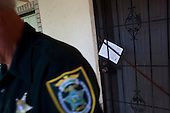 Orlando, Florida<br /> November 12, 2010<br /> <br /> Sheriff's officer Stan Spanich delivers eviction and foreclosure notices throughout Orlando to the wealthy and the poor.
