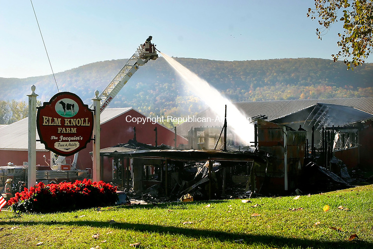 CANAAN, CT-08 OCTOBER 2006-100906JS02-Firefighters from Great Barrington, Mass. using their ladder truck, spray water on hot spots following an early morning fire at Elm Knoll Farm in Cannan on Monday. Firefighters from throughout the Northeast Corner and southwestern Massachuettes were called in to fight the blaze. -Jim Shannon Republican-American