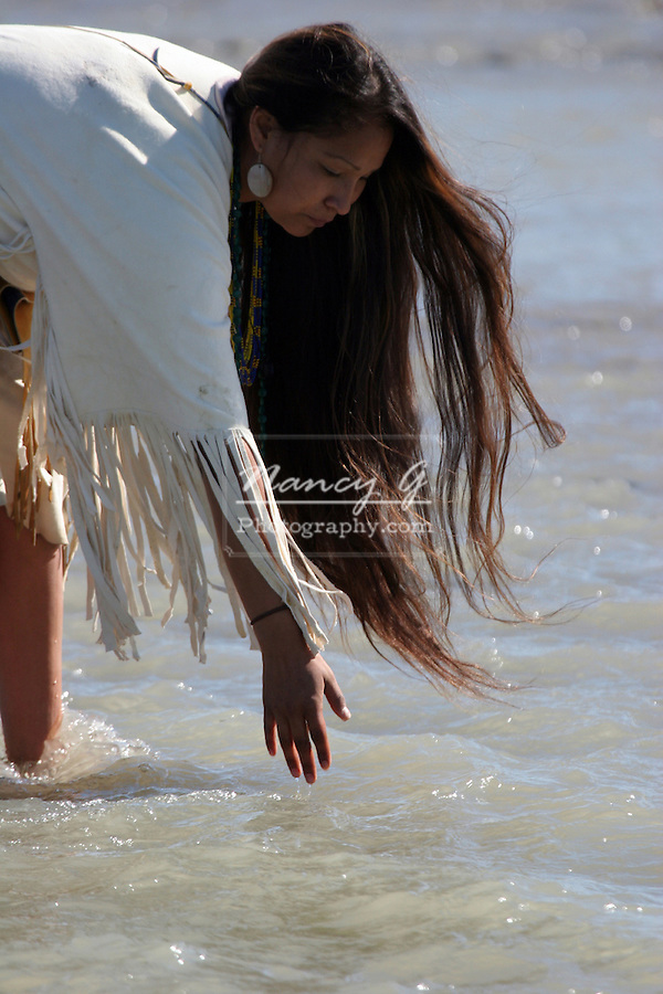 A Native American Indian women dipping her hand in the river of South Dakota