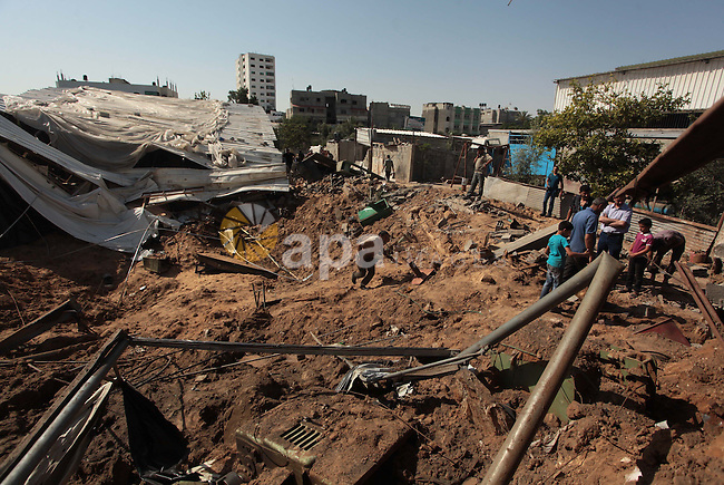 Palestinians inspect the rubble of a destroyed metal workshop after it was hit by an Israeli missile strike in Gaza City, early Tuesday, June 17, 2014. In the Gaza Strip, Israeli warplanes struck three weapons manufacturing and storage sites and another militant site in the Gaza Strip early Tuesday, in response to a rocket launched from Gaza to Israel late Monday, the army said. Photo by Ashraf Amra